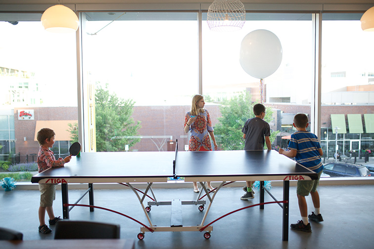 Young boys playing ping pong at E&S new office party